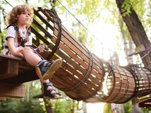 A curly child in climbing safety. Equipment in a tree house or in a rope park climbs the rope. Active children Stock Photo