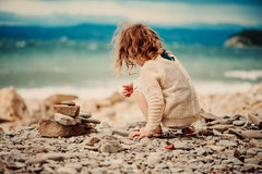 Curly child girl building stone tower on the beach Royalty Free Stock Photos