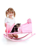 Curly child girl playing with kitten Royalty Free Stock Image