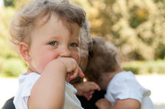 Curly child holds her hand to her mouth at the hands of men Stock Photo
