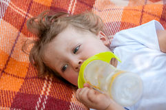Curly child is lying on the coverlet Royalty Free Stock Photography