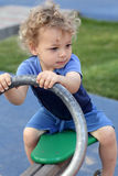 Curly child at seesaw Royalty Free Stock Photo