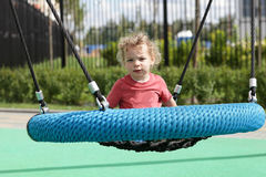 Curly child at swing Royalty Free Stock Photography