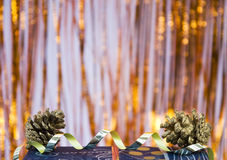 Curly christmas decoration. Part of a christmas gift decorated with a golden curly ribbon and two pine cones, sparkling background Royalty Free Stock Photos