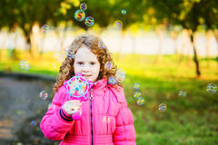 Curly curly  girl blowing soap bubbles Stock Photo
