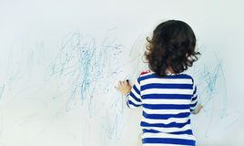 Curly cute little baby girl drawing with crayon color on the wall. Works of child Stock Photography