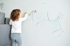 Curly cute little baby girl drawing with crayon color on the wall. Works of child Royalty Free Stock Photo