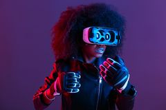 Curly dark haired girl dressed in black leather jacket and gloves uses the virtual reality glasses on her head in the royalty free stock photos