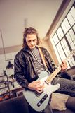 Curly dark-haired rock music player composing new song. Rock music player. Curly dark-haired rock music player wearing leather jacket composing new song royalty free stock photos