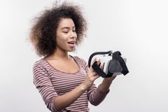 Curly dark-haired woman wearing striped shirt looking at virtual reality glasses royalty free stock photography