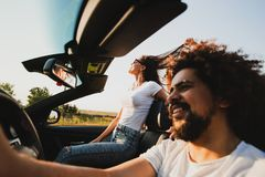 Curly dark-haired young man sitting at the wheel of a black cabriolet and beautiful woman is sitting next to him on a royalty free stock photo