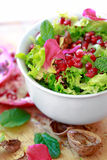 Curly endive salad with pomegranate, nuts, rose petals... Royalty Free Stock Images