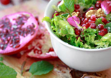 Curly endive salad with pomegranate, nuts, rose petals... Royalty Free Stock Photo