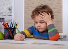 Curly European boy draws sitting at table Royalty Free Stock Image