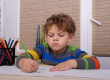 Curly European boy draws sitting at table Royalty Free Stock Images