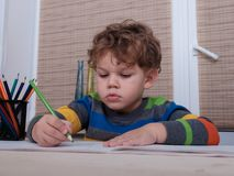 Curly European boy draws sitting at table Royalty Free Stock Photography