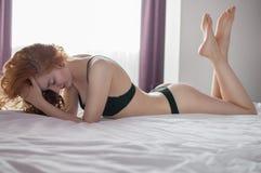 Curly female in black lingerie lying legs crossed on bed Stock Image