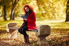 Female reading book in park Royalty Free Stock Photo