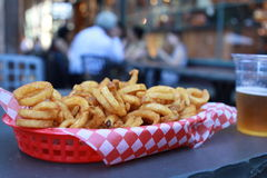 Curly fries with beer served in a restaurant outdoors Royalty Free Stock Photography
