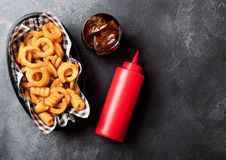 Curly fries fast food snack in red plastic tray with glass of cola and ketchup on stone kitchen background. Unhealthy junk food. Curly fries fast food snack in royalty free stock photo
