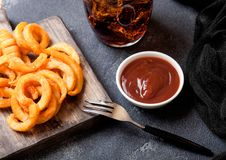 Curly fries fast food snack on wooden board with ketchup and glass of cola on stone kitchen background. Unhealthy junk food. Curly fries fast food snack on royalty free stock images