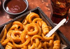 Curly fries fast food snack in wooden box with ketchup and glass of cola on rusty stone kitchen background. Unhealthy junk food. Curly fries fast food snack in royalty free stock photo