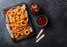 Curly fries fast food snack in wooden with ketchup and glass of cola on stone kitchen background. Unhealthy junk food. Curly fries fast food snack in wooden box royalty free stock photography