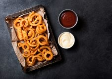 Curly fries fast food snack in wooden with ketchup on stone kitchen background. Unhealthy junk food. Curly fries fast food snack in wooden box with ketchup on royalty free stock images