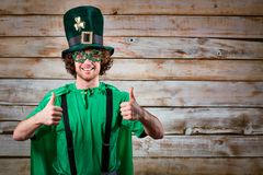 Curly funny man in St. Patrick`s hat . Curly funny man in St. Patrick`s hat on the background of the board Stock Photo