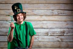 Curly funny man in St. Patrick`s hat . Curly funny man in St. Patrick`s hat on the background of the board Stock Photography