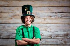 Curly funny man in St. Patrick`s hat . Curly funny man in St. Patrick`s hat on the background of the board Stock Photos