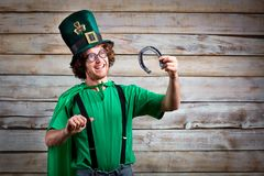 Curly funny man in St. Patrick`s hat . Curly funny man in St. Patrick`s hat on the background of the board Royalty Free Stock Images