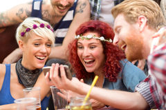Curly ginger girl is delighted with photos on fellows mobile pho Stock Image