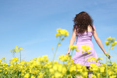 Curly ginger girl in rapeseed field Royalty Free Stock Images