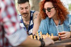 Curly ginger haired female play chess with friends in nature Royalty Free Stock Photo