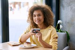 Curly girl with beatiful smile keeping cup of coffee, looking at camera. stock photo