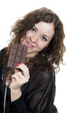 Curly girl in black eating chocolate Royalty Free Stock Images