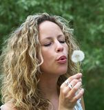 Curly girl blows dandelion Royalty Free Stock Photos