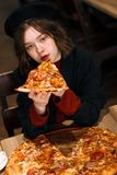 Curly girl with blue eyes eating pizza in cafe royalty free stock photo