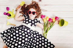 Curly girl with bouquet of tulips lying on white wooden floor. Royalty Free Stock Photo