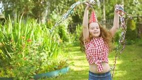 Curly girl in carnival party hat enjoy playing with flying rainbow confetti. In summer park stock footage