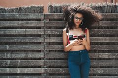Curly girl with cellphone outdoors near wooden wall
