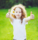 Curly girl with daisy in her hairs, showing thumbs up. Stock Images