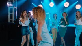 Curly Girl Dancing at party night club. Merry friends of the company. Disco in blue tones, modern youth life. Slow stock footage
