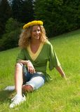 Curly girl with dandelion chain on head Royalty Free Stock Photo