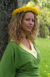 Curly girl with dandelion chain on head Stock Image