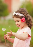 Curly girl with dandelion Royalty Free Stock Image