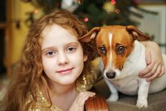 Curly girl embracing puppy jack russell. stock photography