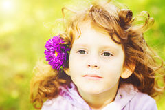 Curly girl with flower in her hair. Toning photo. Instagram filt Stock Images
