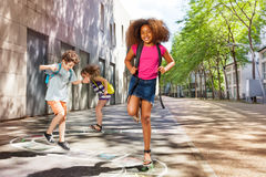 Curly girl with friends jumping hopscotch Royalty Free Stock Images